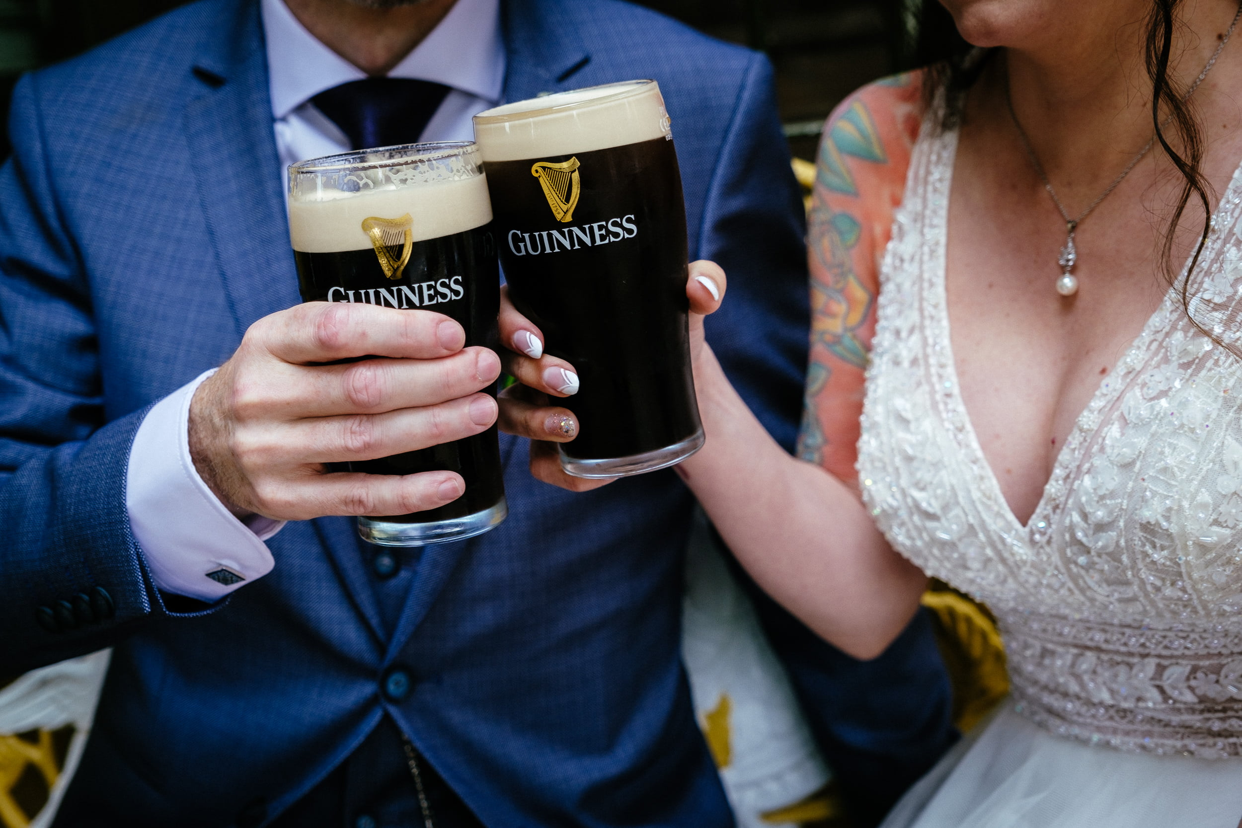 bride and groom drinking a pint of guinness outside the anglers rest in dublin